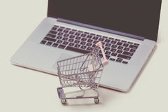 Beautiful shopping cart and cool laptop on the wonderful pink ba Royalty Free Stock Image