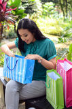 Beautiful shopping woman happy holding shopping bags take rest at garden and smile. Beautiful shopping woman happy holding shopping bags take rest at garden Stock Images