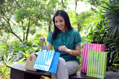 Beautiful shopping woman happy holding shopping bags take rest at garden and smile. Beautiful shopping woman happy holding shopping bags take rest at garden Stock Photography