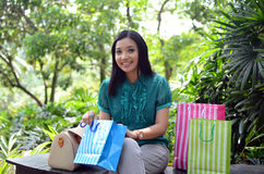 Beautiful shopping woman happy holding shopping bags take rest at garden and smile Stock Photos