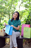 Beautiful shopping woman happy holding shopping bags take rest at garden and smile. Beautiful shopping woman happy holding shopping bags take rest at garden Stock Photo