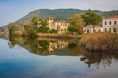 Beautiful shores of Kaifa lake and old ruined buildings and their reflections in water on Peloponnese in Greece. Image of beautiful shores of Kaifa lake and old stock photos