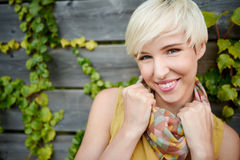 Beautiful short haired platinum blond woman standing against an ivy fence backdrop Stock Photography
