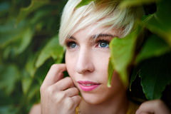 Beautiful short haired platinum blond woman standing against an ivy fence backdrop Royalty Free Stock Images