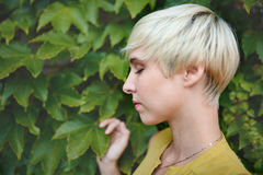 Beautiful short haired platinum blond woman standing against an ivy fence backdrop Royalty Free Stock Photo