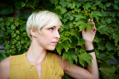 Beautiful short haired platinum blond woman standing against an ivy fence backdrop Royalty Free Stock Photos