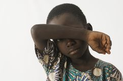 African boy holding his arm in front of his face, as a racism be Stock Images