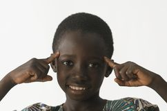 African ethnicity boy thinking with his fingers pointing to his. Beautiful shot of African children taken in a studio in Bamako, Mali Stock Images