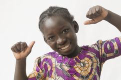 Little African child showing thumbs up, happy girl, isolated on. Beautiful shot of African children taken in a studio in Bamako, Mali Royalty Free Stock Photography