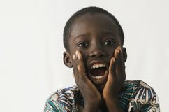 Little African boy surprised holding his mouth open with his han. Beautiful shot of African children taken in a studio in Bamako, Mali Royalty Free Stock Photo