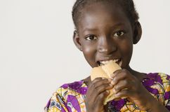 Young African girl eating some bread - isolated on white. Beautiful shot of African children taken in a studio in Bamako, Mali royalty free stock photos