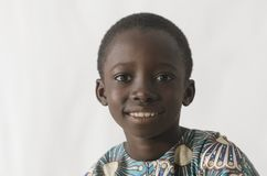 Young African boy smiles at the camera isolated on white stock photos