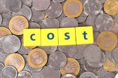 Cost. Beautiful shot of cost spelled on yellow blocks with coins in background Stock Photos