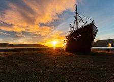 A beautiful shot of a fishing boat approaching the beach at sunrise stock photography