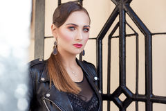 Beautiful shot of a girl with bright trendy makeup in black leather skirt in the style of glam rock. Beautiful shot of a girl with bright trendy makeup in black Stock Photography