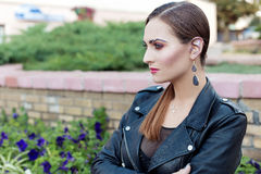 Beautiful shot of a girl with bright trendy makeup in black leather skirt in the style of glam rock. Beautiful shot of a girl with bright trendy makeup in black Stock Photo