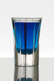 Beautiful shot glass back lit. With a blue drink Stock Images