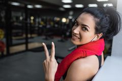 Beautiful shot of happy young beautful fitness woman taking a break from her workout with red towel on neck and earphones stock photography