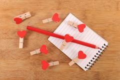 Love clips. Beautiful shot of love clips on wooden background stock photography