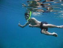 Beautiful shot of male swimming underwater with snorkeling showing thumbs up