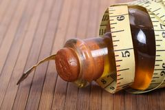 Measuring tape. Beautiful shot of rolled measuring tape on oil bottle Stock Photo
