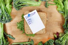 Diet plan. Beautiful shot showing brown bread sandwich with vegetables in border Royalty Free Stock Images