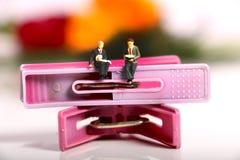 Miniature world. Beautiful shot showing two miniature male sitting on cloth clips Stock Photo