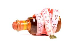 Slimming oil. Beautiful shot of slimming oil bottle with measuring tape Stock Photo