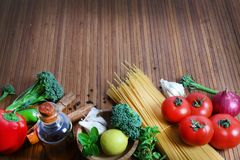 Pasta and ingredients. Beautiful shot of wheat pasta with different types of vegetables on wooden background Royalty Free Stock Photography