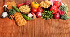 Pasta and ingredients. Beautiful shot of wheat pasta with different types of vegetables on wooden background Stock Photography