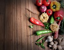 Pasta and vegetables. Beautiful shot of wheat pasta with different types of vegetables on wooden background Stock Photo