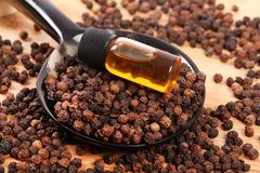 Whole black pepper and oil Royalty Free Stock Photo