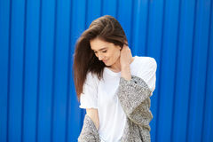 Beautiful shy girl smiling on a blue background stock photo
