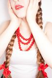 A beautiful shy young folk woman. A beautiful young woman wearing a traditional folk costume with long blonde hair tresses, ribbons and red lipstick Royalty Free Stock Image