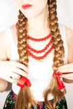 A beautiful shy young folk woman. A beautiful young woman wearing a traditional folk costume with long blonde hair tresses, ribbons and red lipstick Stock Photo