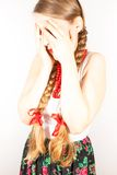 A beautiful shy young folk woman. A beautiful young woman wearing a traditional folk costume with long blonde hair tresses, ribbons and red lipstick Stock Images