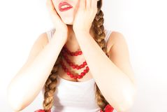 A beautiful shy young folk woman. A beautiful young woman wearing a traditional folk costume with long blonde hair tresses, ribbons and red lipstick Stock Photography