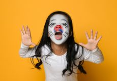 Beautiful sian girl with a painted Korean flag shows tongue and has fun royalty free stock photo