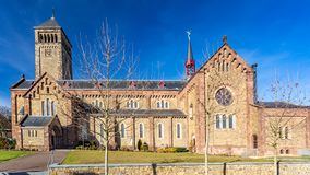 Beautiful side view of a church with its clock in a tower and multiple windows royalty free stock photo