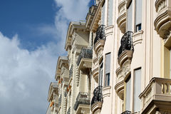 Beautiful sight of building. Menton. France - Month09.2015: Beautiful sight of beige colored building wall with amazing old-fashioned balcony on natural Royalty Free Stock Photography