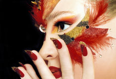 Beautiful sight of the girl. Beautiful sight of the girl in the red make-up,red lips and nails,sequins and feathers stock photography
