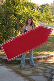 Beautiful Sign Waver or Spinner. Beautiful young lady holds a red directional sign and has a great big smile Royalty Free Stock Photos