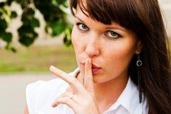 A beautiful silence. Beautiful woman with finger to lips Stock Photo