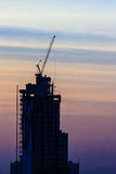 Beautiful silhouette of construction tower cranes with sunset sk Royalty Free Stock Images