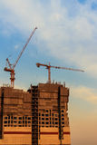 Beautiful silhouette of construction tower cranes with sunset sk Royalty Free Stock Image