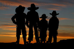 Beautiful silhouette of four young cowboys with a sunset background stock image