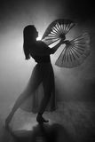 Beautiful silhouette of a girl elegantly dancing in smoke and fog. Stock Photos