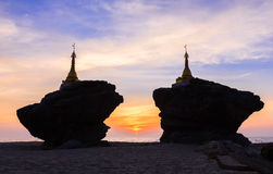 Beautiful silhouette of pagodas on rocks at sea during sunset twilight Stock Photo
