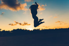 Beautiful silhouette portrait of summer girl jumping on white sand in exotic island at sunset. Serenity, relaxation, mindfulness,. Stress and carefree concepts Royalty Free Stock Photography