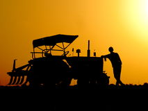 Beautiful silhouette of young farmer with his tractor at evening time in his farm field Royalty Free Stock Image